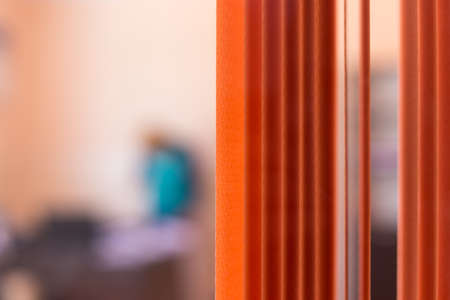 images from an office street, through a window with an orange curtain, silhouette of a man on a blurred background 版權商用圖片