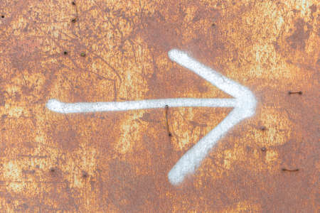 Rusty metal background with arrow and scratches.