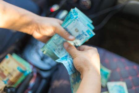 man counts Kazakh money in a car seat