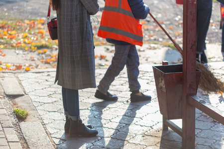 Cleaning lady cleans city sidewalk near bus stops from dead maple leaves