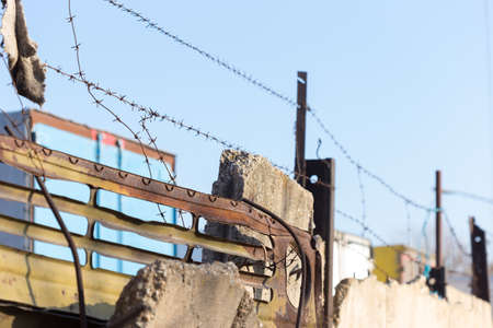 barbed wire with spikes over a concrete fence in the background of blue sky