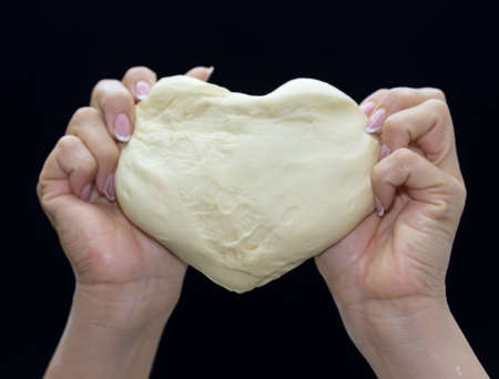 Baker's hands knead the dough on a black background. Heart shaped dough
