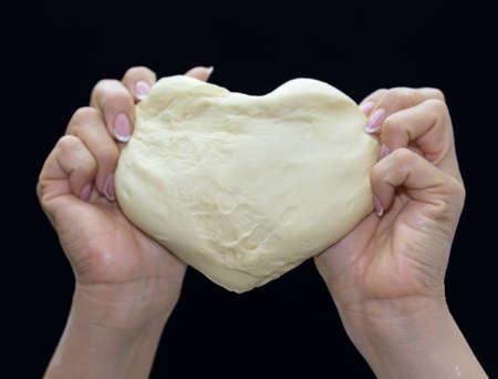 Les mains du boulanger pétrissent la pâte sur fond noir. Pâte en forme de coeur Banque d'images