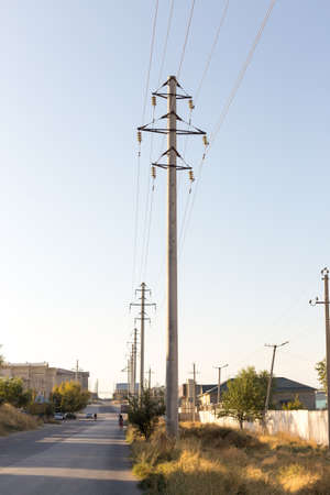 Concrete pillar power lines with steel traverses, porcelain insulators and high-voltage wires on a background of the clear blue sky