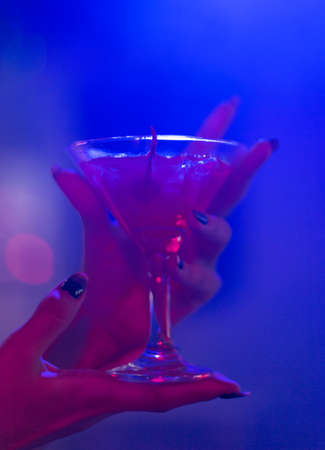 cocktail in the hand of a young girl in a nightclub 스톡 콘텐츠