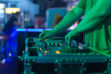 DJ mixing in a karaoke bar. Soft focus on hand - a concept of entertainment, youth, entertainment and relaxation 스톡 콘텐츠