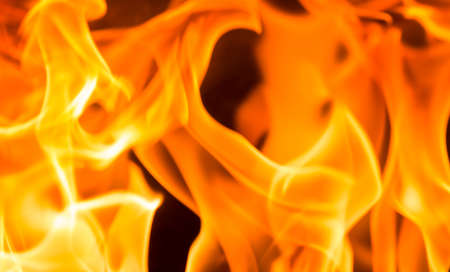 Fire flame burning glowing on black dark background, hot heat energy fuel fire motion pattern abstract texture. 스톡 콘텐츠