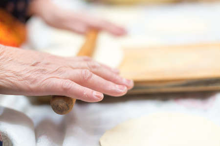 cook, female hand rolls the dough on a wooden board