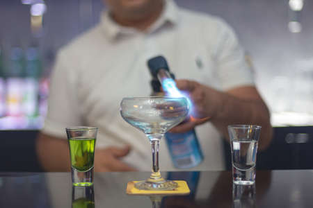 The bartender is lighting a cocktail, a cocktail is lit in a bar