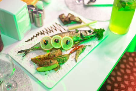 Plate of juicy fish served with french fries and lemon in a restaurant 스톡 콘텐츠