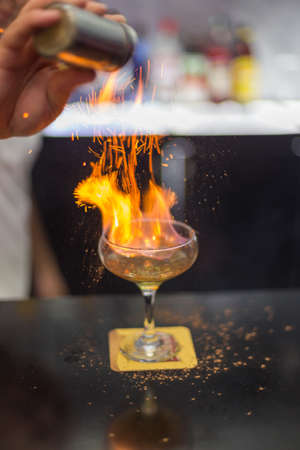 The bartender is lighting a cocktail, a cocktail is lit in a bar Reklamní fotografie