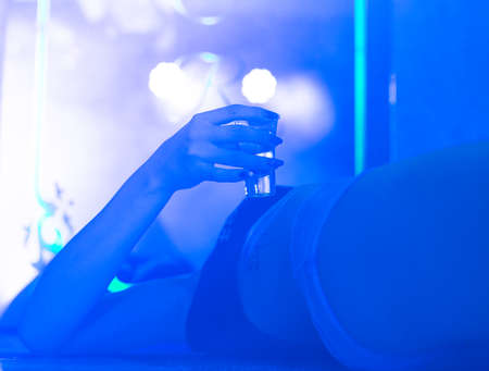Tequila in the hands of a girl who is lying on a table in a nightclub 스톡 콘텐츠