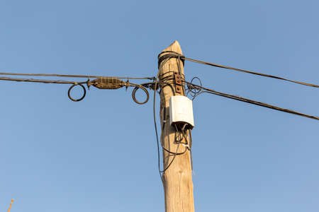 Old-style phone poles and cables. Cables in the air. Clear sky. 스톡 콘텐츠