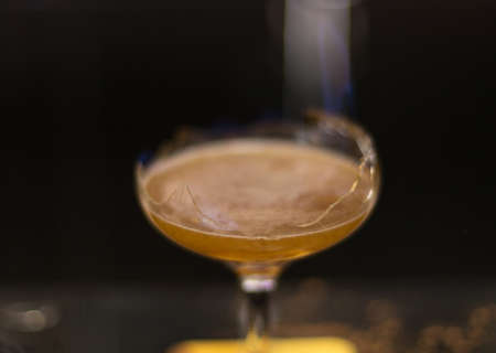 The bartender is lighting a cocktail, a cocktail is lit in a bar 스톡 콘텐츠 - 136251794