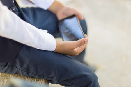 Young boy play online games on a smartphone. Beautiful teenager use phone from side