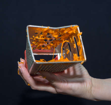 Female hand holds a piece of fresh pumpkin and rubs it on a metal kitchen grater on a black background 스톡 콘텐츠 - 136251886