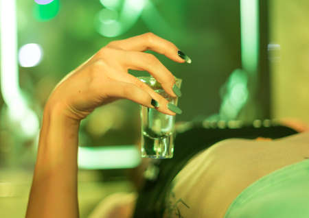 Tequila in the hands of a girl who is lying on a table in a nightclub 스톡 콘텐츠 - 136251891