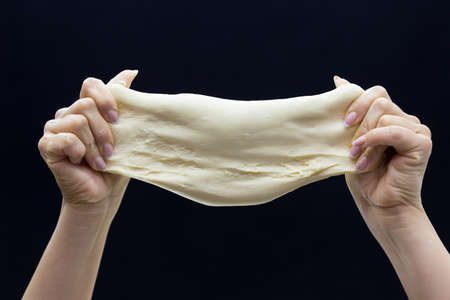 Bakers hands knead the dough on a black background.