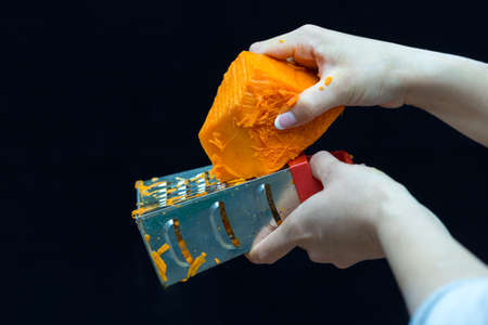 Female hand holds a piece of fresh pumpkin and rubs it on a metal kitchen grater on a black background 스톡 콘텐츠 - 136251938