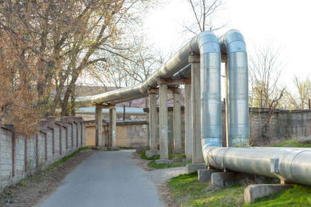 A pipeline above the ground that conducts heat to heat a city. City line in metal insulation in a residential quarter of the city