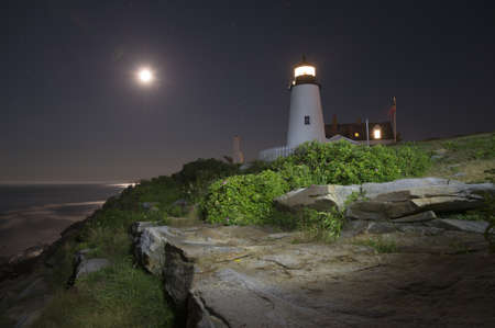 Pemaquid Point Lighthouse at night lit by flashlight and moonlight, Maine, USA photo