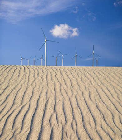 digital composite: Digital composite image of large wind turbines over rippling sand dunes