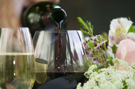 Pouring red wine into a glass sitting on a table in a fine restaurant setting