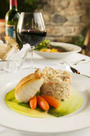Still life of a baked fish seafood dinner on a white plate at a fine restaurant  Archivio Fotografico