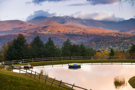 Overlooking a swimming pond with Mt  Mansfield during fall foliage in the background, Stowe, Vermont, USA photo
