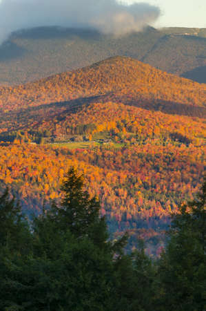 Fall foliage landscape with Trapp Family Lodge and Mt  Mansfield in the background, Stowe, Vermont, USA photo