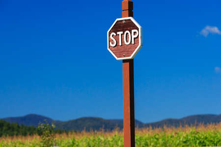 old fashioned: Old fashioned wooden stop sign against a blue sky, Stowe Vermont, USA Stock Photo