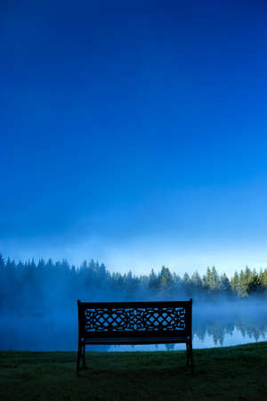 A decorative bench in front of a pond on a blue foggy morning, Stowe Vermont, USA photo