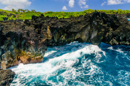 Waves breaking on the rocks on a sunny day during a spectacular ocean view on the Road to Hana, Maui, Hawaii, USA photo