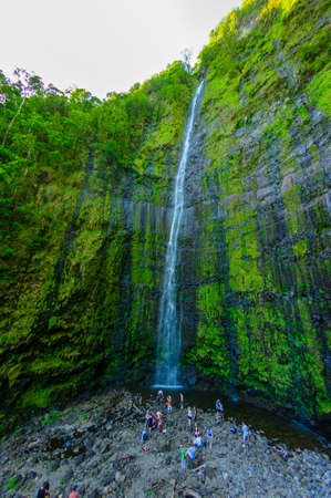 People enjoying the water of Wailua Falls on the Road to Hana, Maui, Hawaii, USA photo