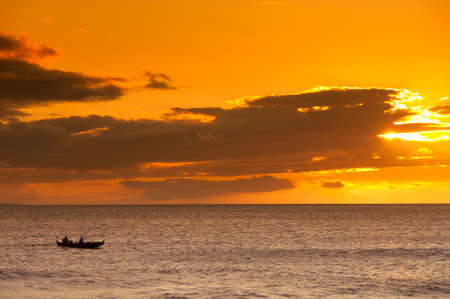 outrigger: Silhouette of two men paddling a Hawaiian outrigger canoe at sunset, Maui, Hawaii, USA