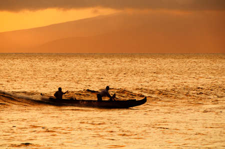 hawaii sunset: Silhouette of two men paddling a Hawaiian outrigger canoe at sunset, Maui, Hawaii, USA