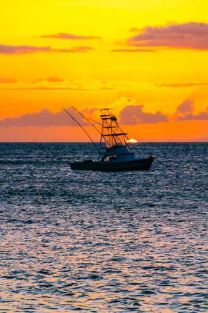 Beautiful sunset behind sport fishing boat with a flying bridge on Maui, Hawaii, USA