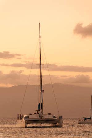 Catamaran cruise boat at sunset on Maui, Hawaii, USA