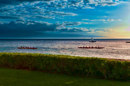 Two native Hawaiian boats rowing past at sunset on Maui, Hawaii, USA photo