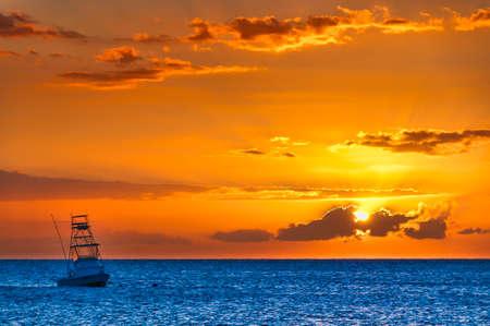 Hermosa puesta de sol detrás de barco de pesca deportiva con un puente de volar en Maui, Hawaii, EE.UU.