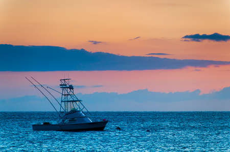 Beautiful sunset behind sport fishing boat with a flying bridge on Maui, Hawaii, USA photo