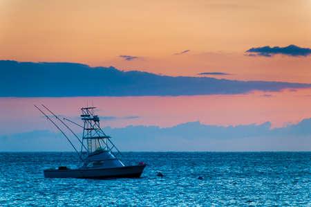 Prachtige zonsondergang achter de sport vissersboot met een vliegende brug op Maui, Hawaii, USA