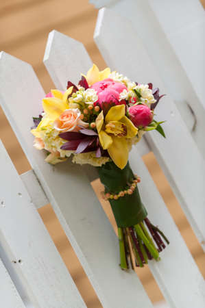 A beautiful bouquet of various flowers on a picket fence  photo