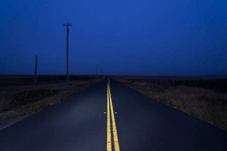 Lonely road at night lit up by head lights in Inverness, California, USA