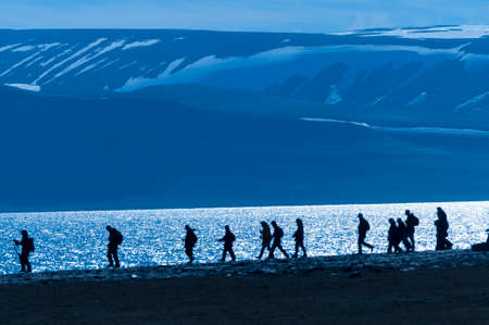 Silhouetted group of hikers along an inlet in Barentsoya, Svalbard, Norway within the arctic circle. photo
