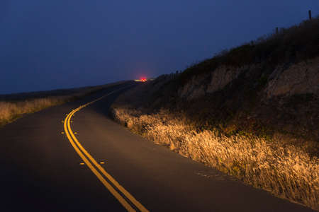 Red car tail lights on a curved road on a foggy night in Inverness, California, USA