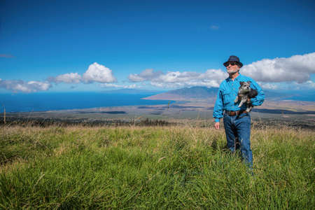 A man in his 60s outdoors holding a small dog