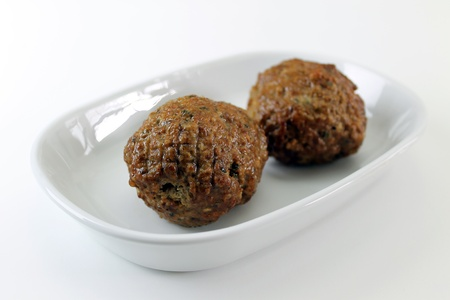 Two meatballs angled on a plate closeup photo