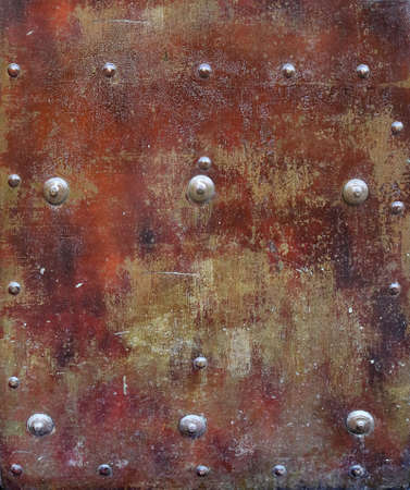 rusty and damaged metal plate with yellow, red and orange tones - worn steampunk background surface with screws and scratches Stock Photo