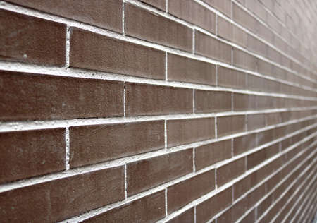 perspective of a big brick wall with dark brown and white color - regular and well aligned bricks background wallpaper